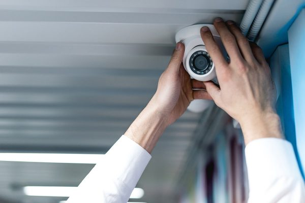 partial-view-of-man-setting-up-security-camera-74G9PFS-min